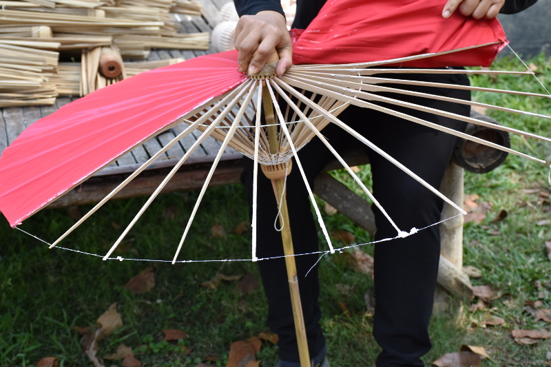 Removing a bamboo umbrella's fabric canopy for replacement