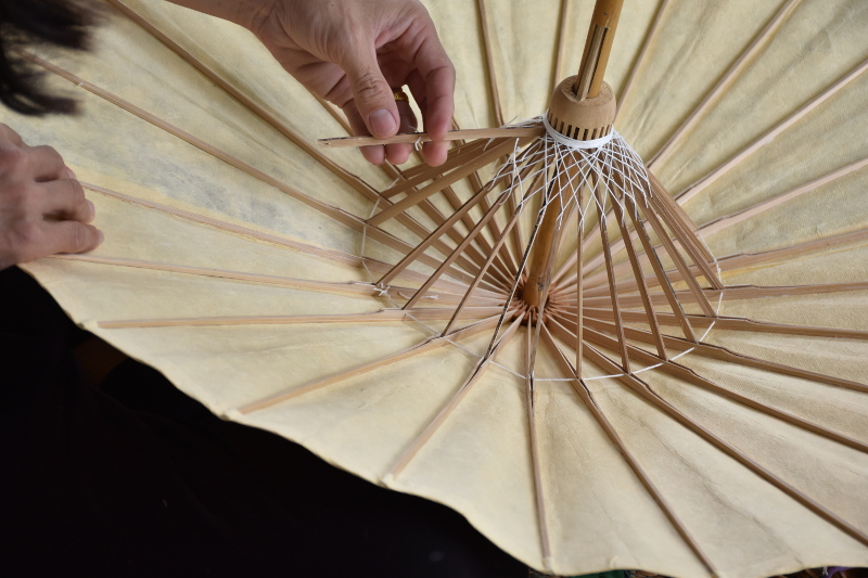 Removing a bamboo umbrella's broken support rib for replacement